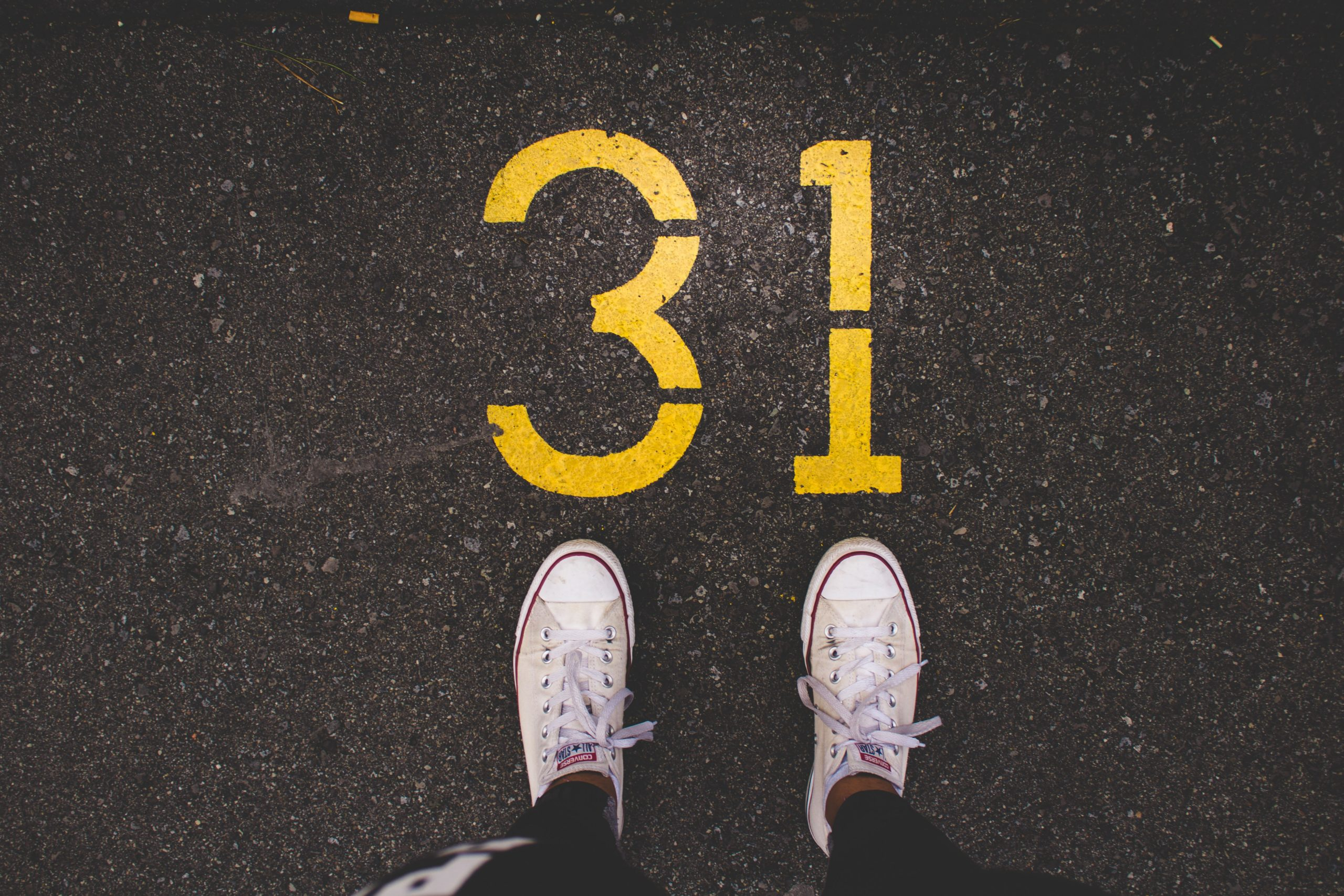 Pair of trainers in front of the number 31 painted on the road