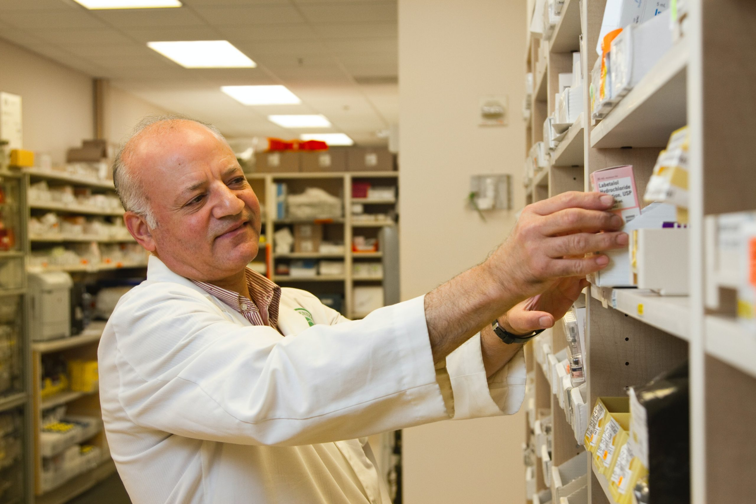 Image of man taking drugs from a shelf in the National Cancer Institute